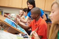 a teacher helps students in a painting class