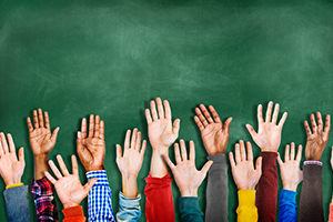 Hands raised in front of a classroom blackboard.