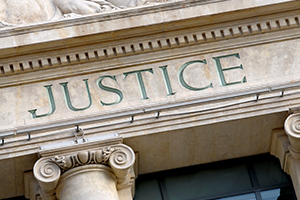 A detail of a building facade, showing the engraved word 'Justice'.