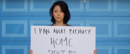 Woman holding up sign saying I ran away because home didn't feel safe.