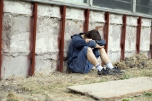 A teenage boy sits against a wall with his head resting on his arms.
