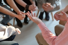 People sitting in a circle. The focus is on their hands; their faces are not visible.