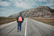 Boy with backpack walking down a country road