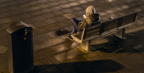 A teenager sitting alone on a bench and using a cell phone.