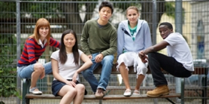 Five youths sitting on a bench
