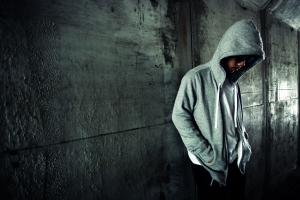 Young man wearing a hoodie standing in tunnel.