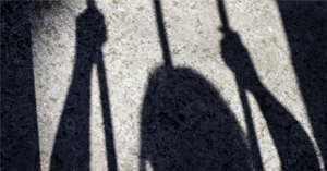 Shadow of a young woman behind bars