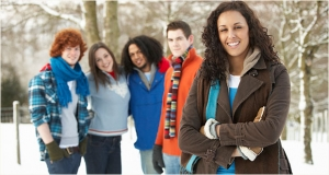 Photograph of diverse young people standing arm in arm.