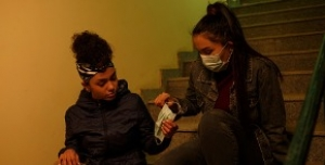 A masked young woman hands a mask to another young woman