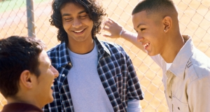 Photograph of three young people talking next to a chain-link fence.