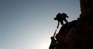 Photograph of a climber helping another person climb a mountain.
