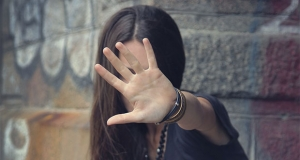 Photograph of a young woman holding up her hand to protect her face.