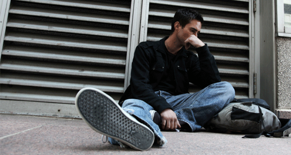 Photo of young man sitting on sidewalk in deep in thought