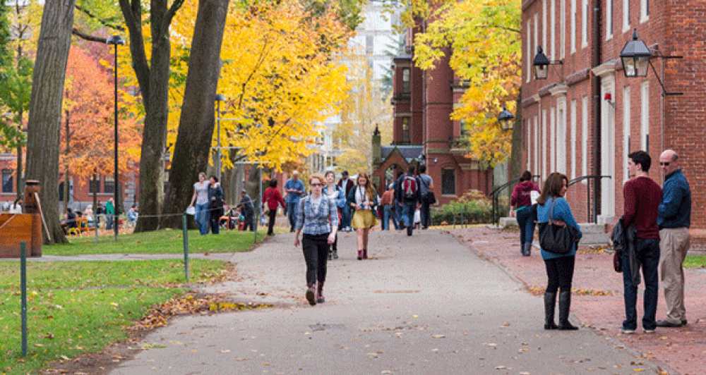 photo of students walking through a college campus with trees in fall colors