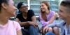 Two teen boys and teen girls sitting together on steps.