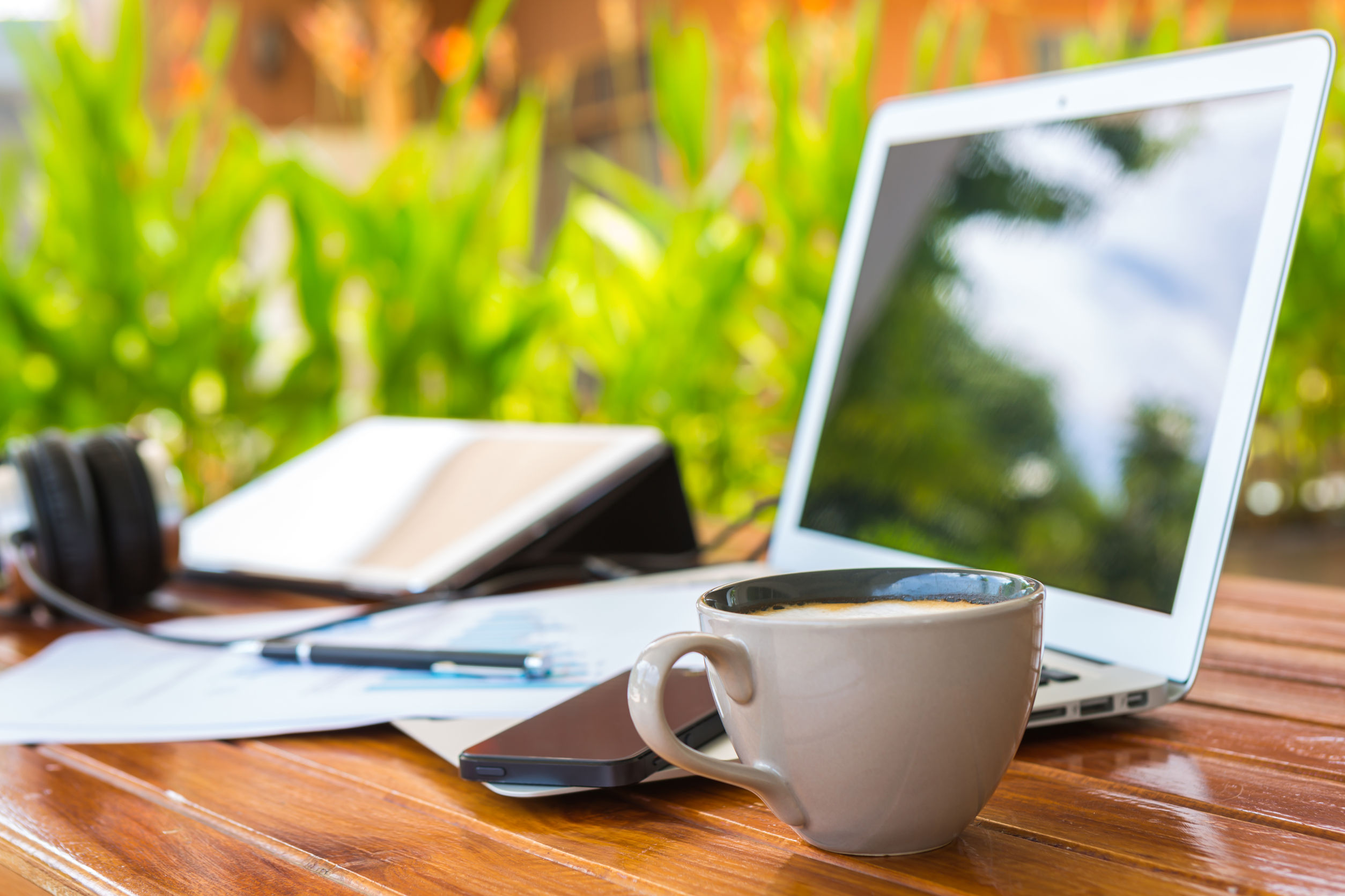 An open laptop and cup of coffee on a desk
