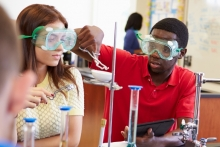 Two high school students conducting an experiment in chemistry class