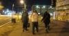 A group of homeless youths walking on a sidewalk at night.