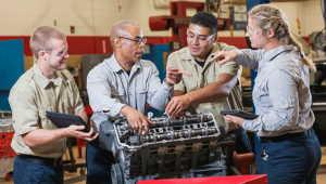 Photo of three students listening to an instructor as they look at an engine at a technical school